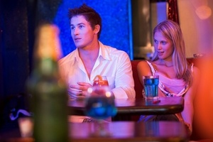 Young woman looking at a young man in a nightclub